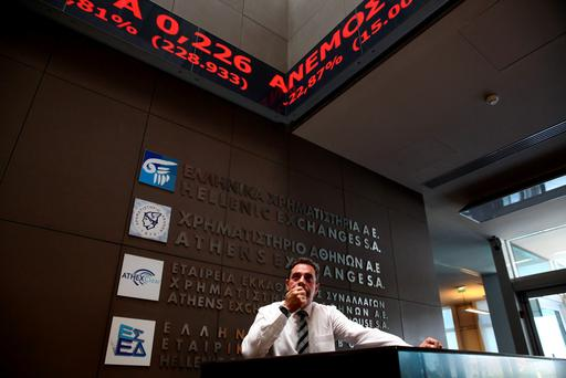 An employee looks on at electronic board displaying stock prices at the entrance of the Athens Stock Exchange, Greece, August 3, 2015. Greece's stock market plunged nearly 23 percent on Monday when it opened after a five-week shutdown brought on by fears the country was about to be dumped from the euro zone. REUTERS/Yiannis Kourtoglou