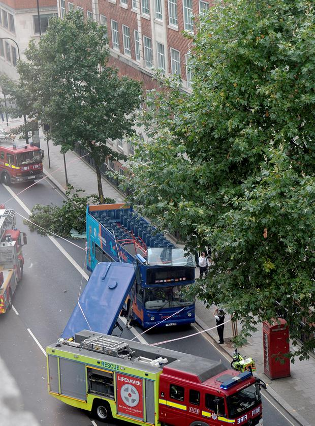Emergency services attend the scene after a double decker bus had its roof ripped off when it crashed into a tree in Woburn Place, Bloomsbury, central London. Anthony Devlin/PA Wire