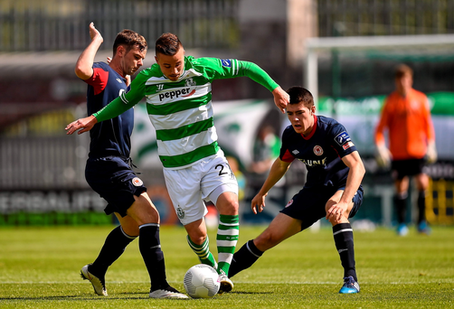 Mikey Drennan of Shamrock Rovers, powers through two opposing players