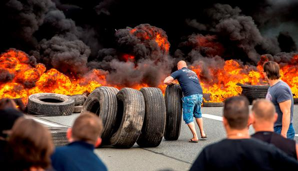Striking employees of a ferry company blocked the access to the harbour in Calais by setting tyres on fire after talks over job cuts failed. The fires added to the chaos created by the clampdown on illegal migrants entering the Channel Tunnel