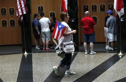 A woman carries the Puerto Rico flag as she walks inside the National Baseball Hall of Fame in Cooperstown, New York, July 24, 2011. REUTERS/Mike Segar