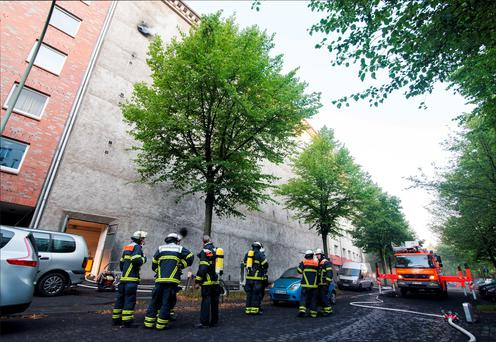 Firefighters stand outside a WWII bunker that got on fire on August 4, 2015 in Hamburg amid an explosion that wounded 21 people. Photo: AFP/Getty Images