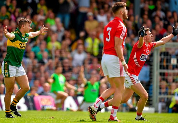 James O'Donoghue, left, and Cork's Mark Collins both react before referee Padraig Hughes awarded Kerry a controversial penalty in the drawn Munster final