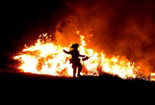 A Cal Fire firefighter uses a drip torch to start a backfire as he battles the Rocky Fire near Clearlake, California. Photo: Getty Images