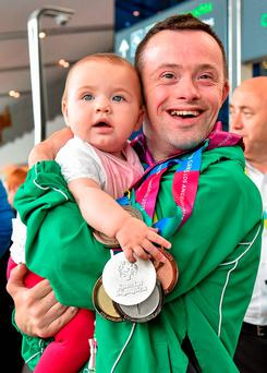 4 August 2015; Team Ireland's Paul Keane, from Ferns, Co. Wexford, reunites with his niece Mila Keane, age 6 months, after earning five medals: a gold, three silvers and a bronze plus two ribbons in gymnastics at Dublin Airport during their homecoming. Team Ireland returns from the Special Olympics World Summer Games. Terminal 1, Dublin Airport. Picture credit: Cody Glenn / SPORTSFILE