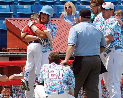 Nine-year-old bat boy Kaiser is seen being hugged by Liberal Bee Jays outfielder Gavin Wehby in Kansas on Saturday - just seconds after he was struck. Credit; AP