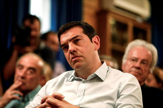 Greece's Prime minister Alexis Tsipras listens to a speech during a gathering at the Agriculture ministry in Athens, Greece, on Wednesday, Aug. 5, 2015. Tsipras said his country was at the final stage of talks for a new bailout, as his left-wing government on Wednesday rejected the idea of an extension in negotiations. (AP Photo/Yorgos Karahalis)