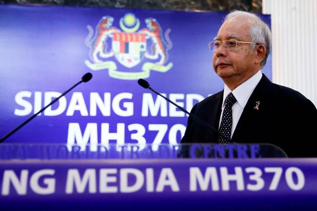 Malaysian Prime Minister Najib Razak, center, arrives for a special press conference announcing the findings for the ill fated flight MH370 in Kuala Lumpur, Malaysia (AP Photo/Vincent Thian)