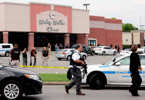 Police work outside a movie theater complex where officials reported a man with at least one gun and a weapon described as a hatchet was killed by police on Wednesday, Aug. 5, 2015, in Antioch, Tenn. (AP Photo/Mark Humphrey)