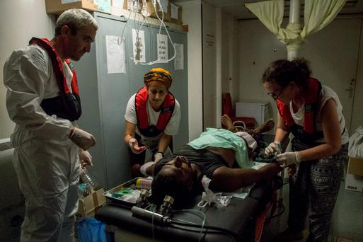 The MSF medical team on board the Dignity I search and rescue vessel provides first aid to a Bangladeshi man with an open fracture of his leg who was earlier rescued from the sea water after the boat he was in with other migrants capsized and sank in the Mediterranean 05 August. (Photo: Marta Soszynska/MSF)