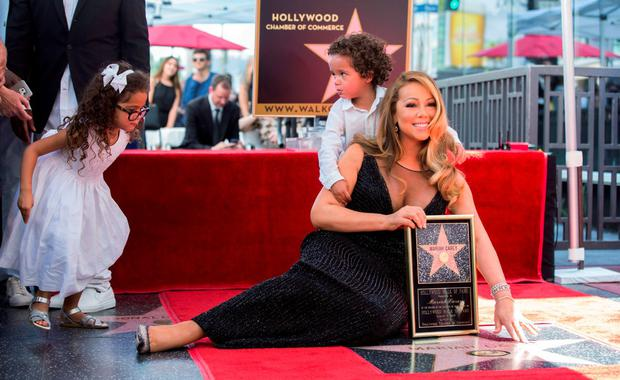 Recording artist Mariah Carey poses on her star with her children Moroccan Scott and Monroe Cannon after it was unveiled on the Hollywood Walk of Fame