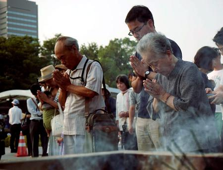 Visitors pray for the atomic bomb victims in front of the cenotaph at the Hiroshima Peace Memorial Park in Hiroshima, western Japan, Thursday, Aug. 6, 2015. (AP Photo/Koji Ueda)