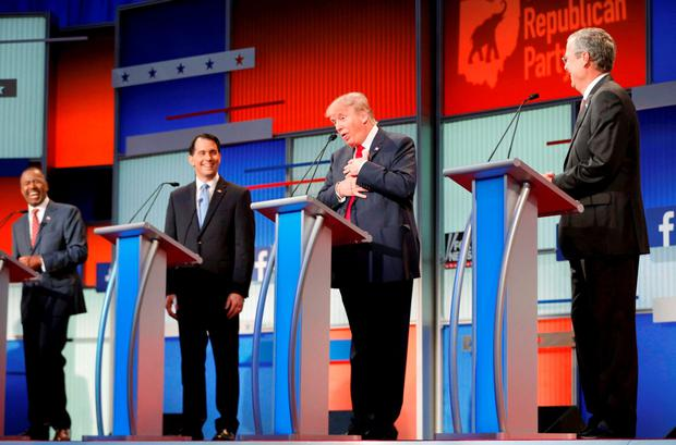 Fellow Republican 2016 U.S. presidential candidates Dr. Ben Carson (L), Wisconsin Governor Scott Walker (2nd L) and former Florida Governor Jeb Bush (R) laugh as fellow candidate and businessman Donald Trump (2nd R) reacts near the end of the debate after realizing that a slew of criticisms spoken by fellow candidate and former Arkansas Governor Mike Huckabee (not pictured) were not aimed at him but at Democratic presidential candidate Hillary Clinton. REUTERS/Brian Snyder