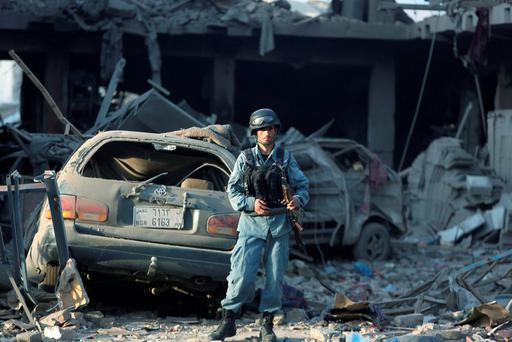 An Afghan policeman stands guard at the site of a car bomb attack in Kabul, Afghanistan. (AP Photo/Rahmat Gul)