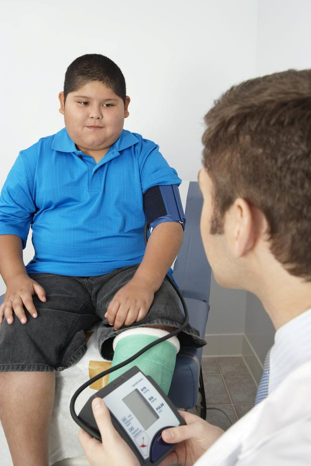 Boy having his blood pressure checked by doctor