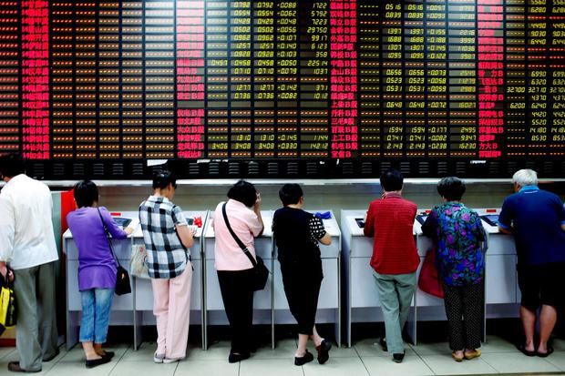 Investors look at computer screens showing stock information at a brokerage house in Shanghai. Photo: Reuters