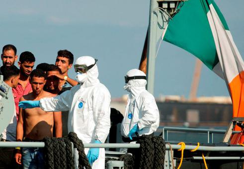 A rescuers gestures as migrants wait to disembark from the Irish military vessel Le Naimh after its arrival in the port of Palermo this week.