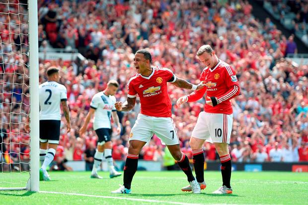 Manchester United's Wayne Rooney and Memphis Depay (centre) celebrate Tottenham Hotspur's Kyle Walker (background, left) scoring an own goal during the Barclays Premier League match at Old Trafford, Manchester