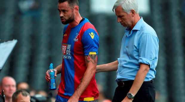 Crystal Palace's Damien Delaney leaves the field after picking up an injury as manager Alan Pardew looks on