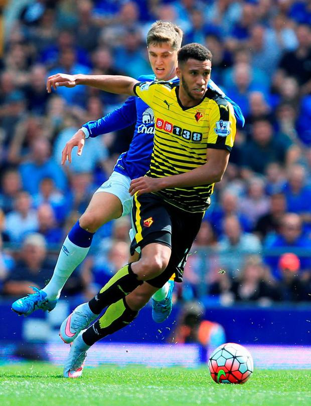 Etienne Capoue of Watford powers past Everton's in-demand defender John Stones