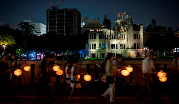 Light in the darkness: People carry lanterns past the Genbaku dome at the Hiroshima Peace Memorial Park on Wednesday.