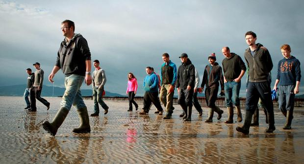 Derek Diver left and his wife Sharon with the fishermen who are employed at his oyster farm, pictured in the background on Linsfort Beach, in Co Donegal, (Photo;Cristeph/Brian McDaid)