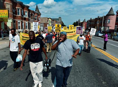 Andre Powell, left, an organizer with Baltimore People's Power Assembly, and Rev. C.D. Witherspoon, president of the Baltimore SCLC, lead a march on North Avenue in Baltimore, Saturday, Aug. 8 2015, the eve of the anniversary of Michael Brown's death during a confrontation with a police officer. (Kim Hairston/The Baltimore Sun via AP)