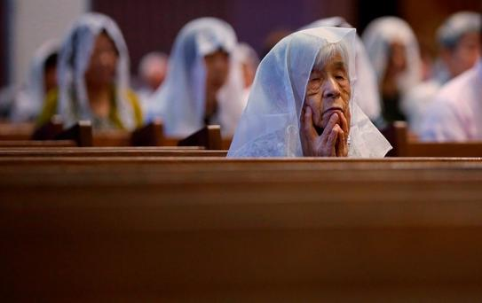 Catholics listen the preaching at an early morning mass to pay respect to the victims of the Nagasaki atomic bombing at the Urakami Cathedral in Nagasaki, southern Japan Sunday, Aug. 9, 2015. (AP Photo/Eugene Hoshiko)