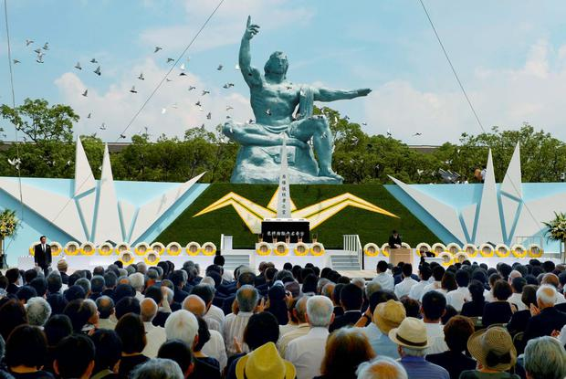Doves fly over the Peace Statue in Nagasaki's Peace Park during a ceremony commemorating the 70th anniversary of the bombing of the city, in Nagasaki, western Japan, in this photo taken by Kyodo August 9, 2015. REUTERS/Kyodo