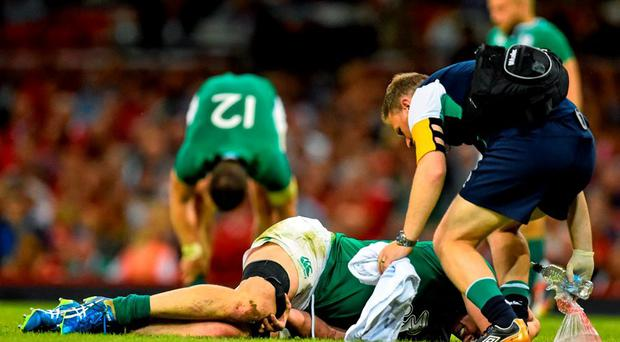 Tommy O'Donnell, Ireland, is treated for an injury, before leaving the pitch on a stretcher. Rugby World Cup Warm-Up Match, Wales v Ireland, Millennium Stadium, Cardiff, Wales. Picture credit: Ramsey Cardy / SPORTSFILE