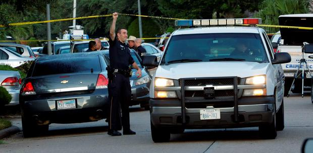 A member of the Harris County Sheriff's Department raises the crime scene tape for a vehicle outside the scene of shooting (AP Photo/David J. Phillip)