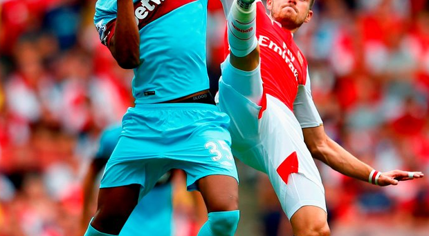 Reece Oxford of West Ham United and Aaron Ramsey of Arsenal in action