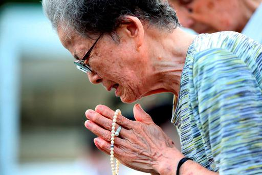 A woman cries as she prays at the Peace Park before the 70th anniversary of the Nagasaki atomic bombing in Nagasaki, Japan