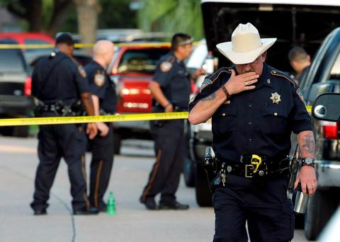 Harris County Sheriff's Department Sgt. D.J. Hilborn, right, walks away from the scene of a multiple shooting in Houston
