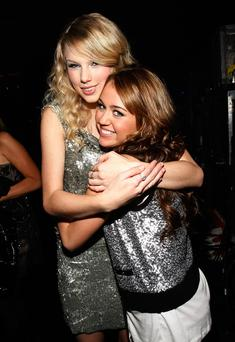 Singers Taylor Swift (L) and Miley Cyrus pose backstage at the 2008 American Music Awards held at Nokia Theatre L.A. LIVE on November 23, 2008 in Los Angeles, California.