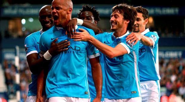 Manchester City's Vincent Kompany (second left) celebrates scoring his side's third goal of the game with his teammates during the Barclays Premier League match at The Hawthorns