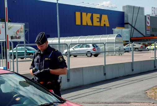 A police office talks to customers outside the Ikea store in Vasteras, Sweden. Photo: Peter Kruger/TT via AP