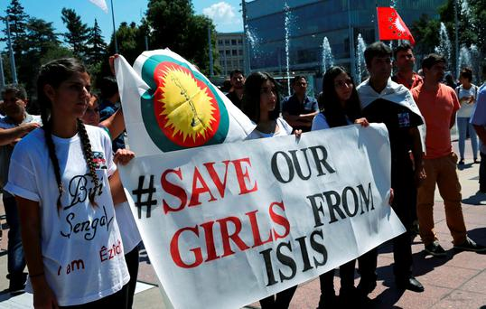 Women hold a banner during a demonstration marking the first anniversary of Islamic State's surge on Yazidis of the town of Sinjar, in front of the United Nations European headquarters in Geneva, Switzerland. Photo: Reuters
