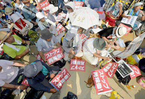 Protesters stage a sit-in in front of an entrance gate of Kyushu Electric Power's Sendai nuclear power station in Satsumasendai, Kagoshima prefecture REUTERS/Kyodo