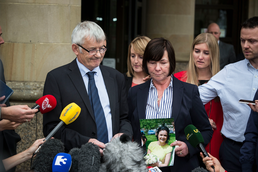 John Buckley gives a statement following today's court proceedings, while Marian holds a photo of their daughter Karen.