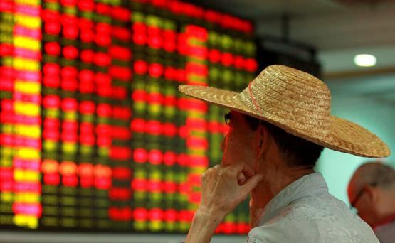 An investor looks at an electric board showing stock information at a brokerage house in Haikou, Hainan province, China. Photo: Reuters