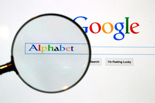 A Google search page is seen through a magnifying glass in this photo illustration taken in Berlin, August 11, 2015. Google Inc is changing its operating structure by setting up a new company called Alphabet Inc, which will include the search business and a number of other units. REUTERS/Pawel Kopczynski