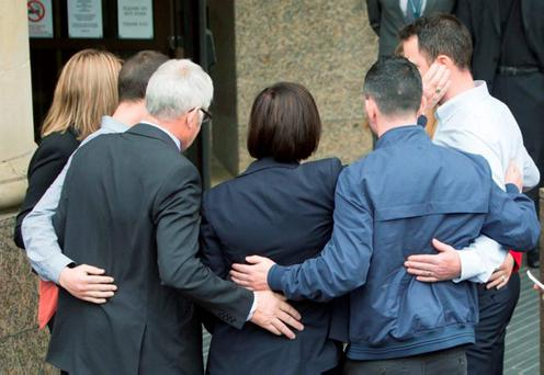 John Buckley hugs his wife Marian Buckley and their three sons outside Glasgow High Court