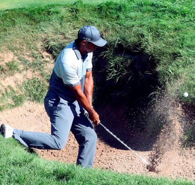 Tiger Woods hits out of a bunker during a practice round at Whistling Straits yesterday
