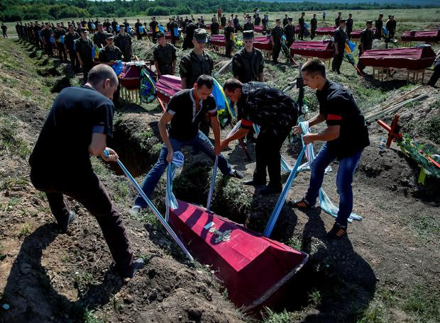 Workers take part in a mass funeral ceremony to bury 57 unidentified members of Ukrainian military forces who were killed in the conflict in eastern regions, in the settlement of Kushuhum near Zaporizhia. Photo: Reuters