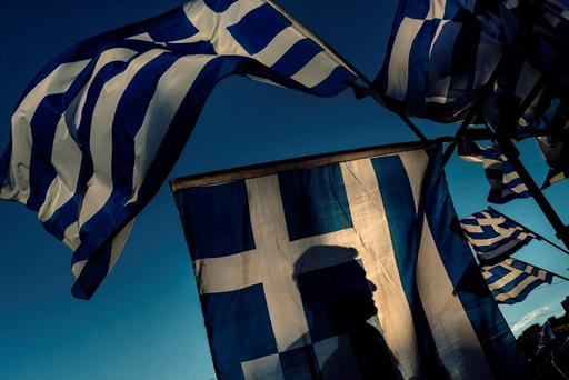 A pro-Euro demonstrator is silhouetted behind a Greek flag during a rally outside the Greek Parliament in Athens, in this photo dated Monday, June 22, 2015. (AP Photo/Daniel Ochoa de Olza)