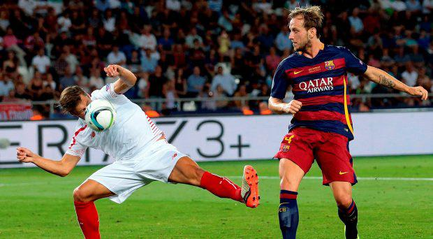Sevillas Grzegorz Krychowiak, left, stops with his face a shot at goal from Barcelona's Ivan Rakitic, right, during the UEFA Super Cup soccer match between FC Barcelona and Sevilla FC at the Boris Paichadze Dinamo Arena stadium, in Tbilisi, Georgia, on Wednesday, Aug. 12, 2015. (AP Photo/Ivan Sekretarev)
