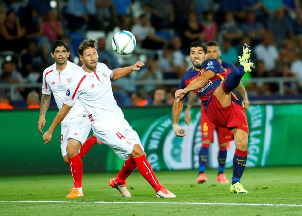 Barcelona's Luis Suarez (R) and Sevilla's Grzegorz Krychowiak look at the ball during their UEFA Super Cup soccer match at Boris Paichadze Dinamo Arena in Tbilisi, Georgia, August 11, 2015. REUTERS/David Mdzinarishvili