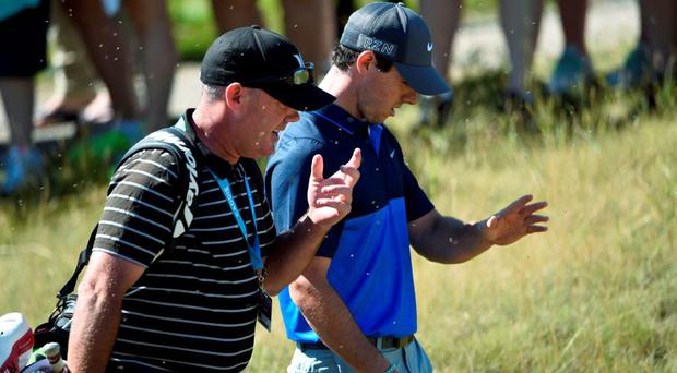 Rory McIlroy (right) and Michael Bennett the caddie for James Hahn walk through a swarm of bugs during a practice round at Whistling Straits