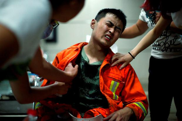 A firefighter reacts as he receives treatment at a hospital after the explosions at the Binhai new district in Tianjin, China REUTERS/China Daily